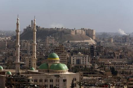منظر عام يظهر صعود عمود من الدخان من موقع بالقرب من قلعة حلب في مدينة حلب السورية يوم السبت. تصوير: عمر صناديقي - رويترز