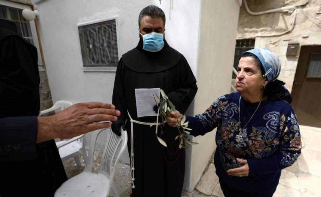 رهبان يقدمون أغصان الزيتون للمسيحيين في القدس الخالية من المارة في أحد السعف